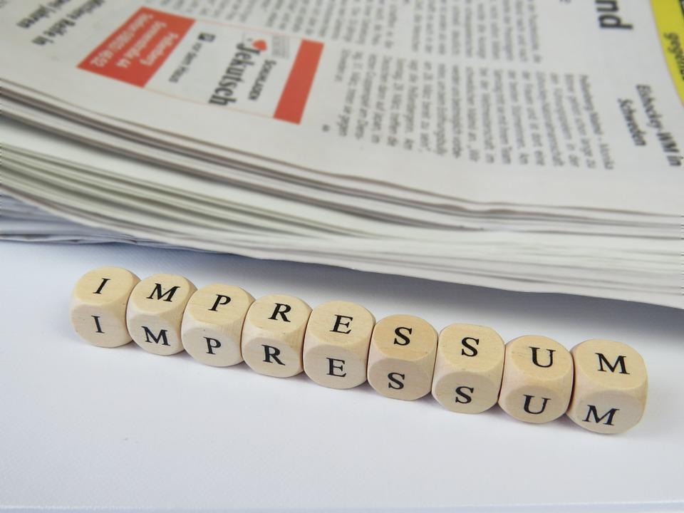 Impressum - NITSA e.V. - Würfel mit der Aufschrift Impressum vor einer Zeitung