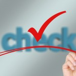 """Bild zeigt eine Hand, die einen Haken unterstreicht. Im Hintergrund steht """"check""""."""